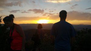 three tourists watching sunset almost dark