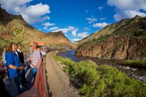Tourists outside on Royal Gorge train moving near river with blue sky