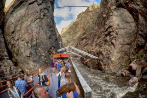 tourists on train deck going through mountains in Colorado