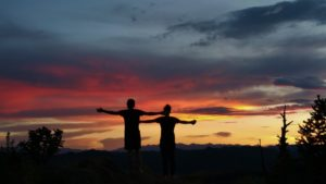 Two people creating silhouette behind pink blue and gold sunset in Colorado