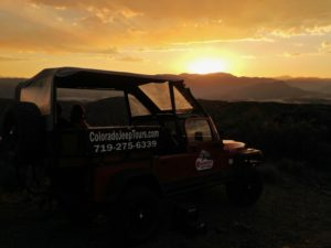 Sunset almost down over mountains with Jeep tour vehicle in foreground