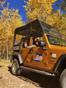 Jeep Tour passenger waving at camera with Aspen trees in background