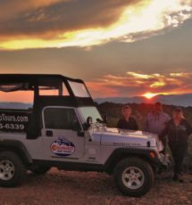 tourists outside jeep enjoying the sunset over the mountains during a Colorado Jeep Tour