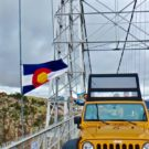 tourist waving from jeep while driving over Royal Gorge bridge and Colorado Flag