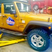 Gold Jeep getting new Cooper Tires