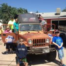 family posing around Jeep during a Colorado Jeep Tour