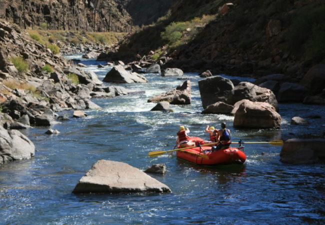 guests enjoying whitewater rafting trip on a sunny day