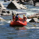 two guests and guide enjoying whitewater rafting trip