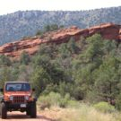 Jeep driving on road with red rocks in background Colorado Jeep Tours