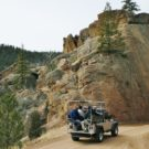 silver jeep with passengers driving through mountain pass