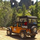 guests driving down dirt road on sunny day during Colorado Jeep Tour