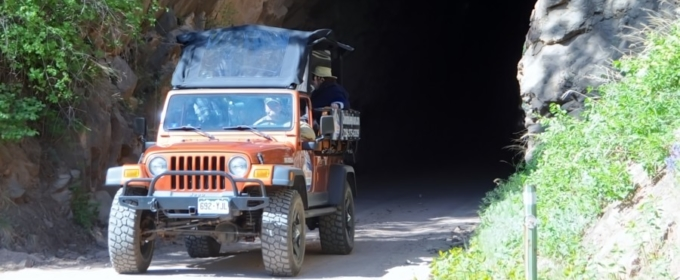 Colorado Jeep Tour-jeep with guests driving out of tunnel on a sunny day