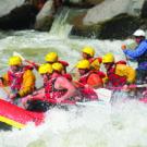 group navigating waves during whitewater rafting tour