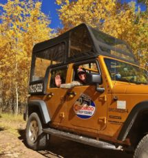 Colorado Jeep Tours guide waving from jeep with yellow leaves in background