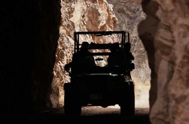 silhouette view of jeep driving through tunnel
