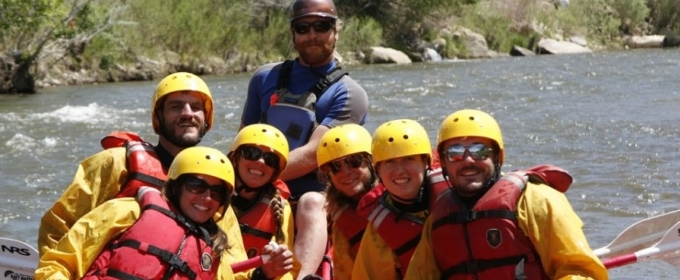 whitewater rafting tour group and guide posing for photo